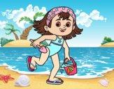 Menina com praia balde e pá